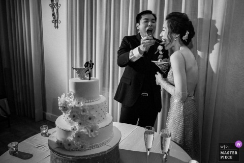 Bride and groom feed each other cake at the wedding reception at the Castlewood Country Club in Pleasanton