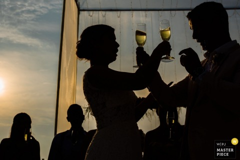 Bride and groom cross arms with their drinks at the wedding reception in Lima, Peru