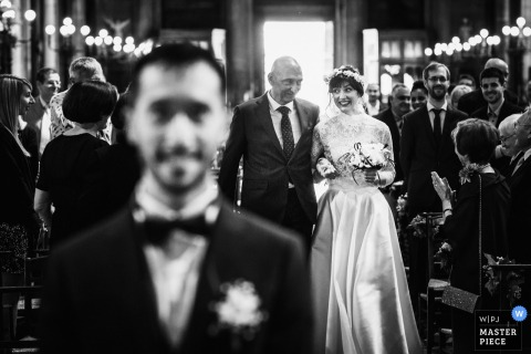 Groom smiles as the bride and her father walk down the aisle at the wedding ceremony in Paris, France
