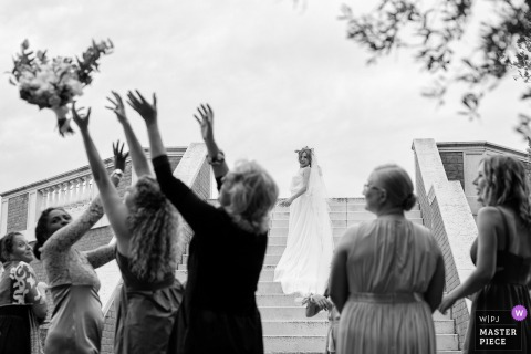 Guests reach for the bouquet at the wedding reception in Armeni Island - Venice - Italy