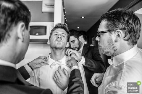De groomsmen helpen de bruidegom met zijn overhemdkraag en stropdas vóór de ceremonie in Camaret sur Mer, Frankrijk