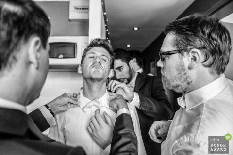The groomsmen help the groom with his shirt collar and tie before the ceremony at Camaret sur Mer, France