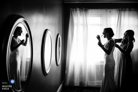 Bruid die hulp van bruidsmeisje met haar kleding krijgt vóór de huwelijksceremonie in Voorzienigheid, Rhode Island