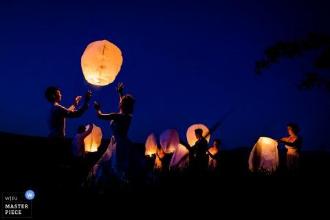 Bruid en bruidegom die klaar om lantaarns buiten bij nacht in Greensboro, Vermont worden vrij te geven