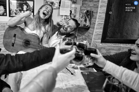 Bridal party enjoy drinks while bride and groom sing in Kiev, Ukraine