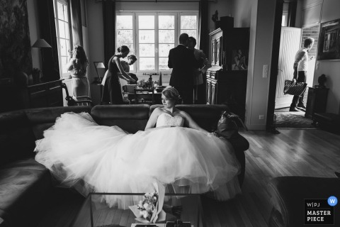 Paris bride sits on the couch in her wedding dress before the wedding