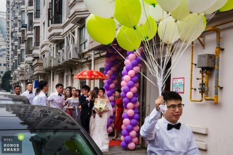 Brautpartei geht die Straße in China mit Ballons und einem roten Regenschirm entlang