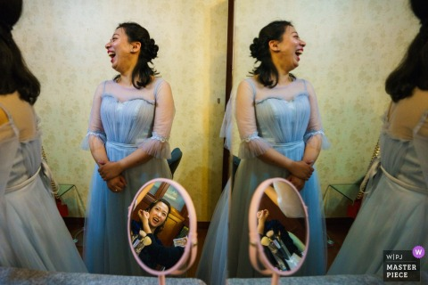 Bridesmaid and bride laugh as they get ready for the wedding ceremony in China