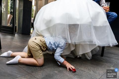 Little boy underneath the bride in her wedding dress at the wedding in Denekamp