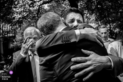 Groom and groomsmen hug and get emotional during the wedding in De Lutte