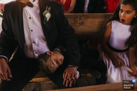 Little boy sleeps on fathers lap at the wedding ceremony in San Miguel, Mexico