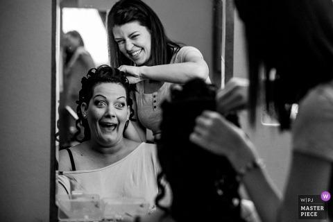 De bruid die van Hongarije haar haar krijgt die in de spiegel vóór de huwelijksceremonie wordt gedaan