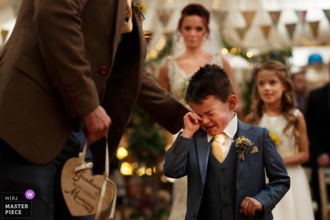 Kleine jongen die huilt tijdens de huwelijksceremonie bij de Wellbeing Farms