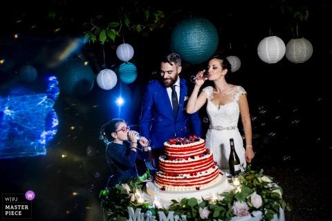 De bruid en de bruidegom van Italië met bloemmeisje voor de huwelijkscake bij de huwelijksontvangst