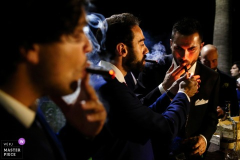 Calabria groom and groomsmen smoke at the wedding reception