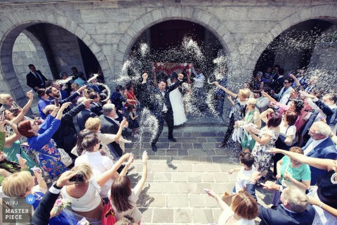 Guests throw rice outside at the bride and groom after the wedding ceremony in Parrocchia Regina Pacis, Saronno, Italy
