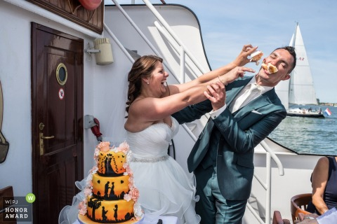 Bride smashes cake into the grooms face on a boat wedding reception in IJsselmeer
