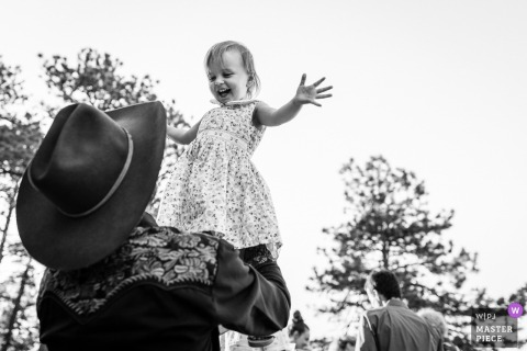 Cowboy at Sunrise Amphitheater outdoor wedding reception throws daughter into the air.