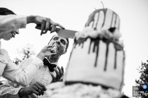 Braut wendet Messer und Kuchen Hochzeit an im Freien in Boulder, Colorado an. Braut zwingt Hochzeitstorte in den Mund des Bräutigams. Sonnenaufgang-Amphitheater, Boulder, Colorado