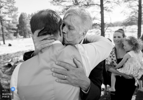 Outdoor photo of the groom and his father hugging at the wedding in Flagstaff, Arizona