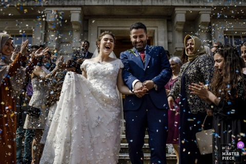 Guests throw rice at the bride and groom after the wedding ceremony outside in London, UK