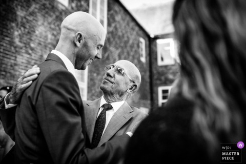 Photo of the groom hugging and smiling with his father at the wedding at the Fulham Palace, London, UK