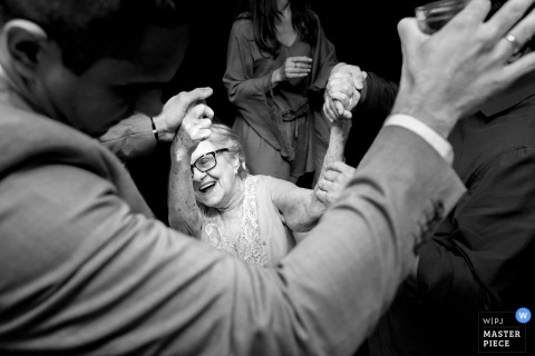 Groom dances with elderly lady at the wedding reception in Rio de Janeiro, Brazil