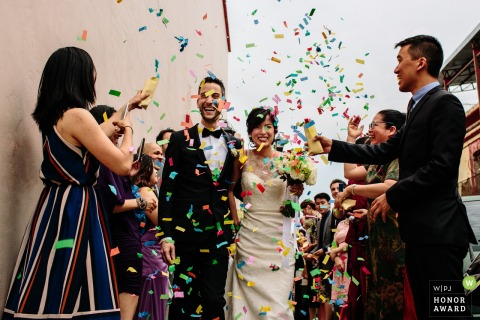 Oaxaca City, Oaxaca, Mexico bride and groom under a rainbow colored shower of confetti