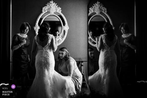 Brautjungfern, die der Braut mit ihrem Kleid vor einem Spiegel vor der Hochzeitszeremonie in Wexford, Irland helfen