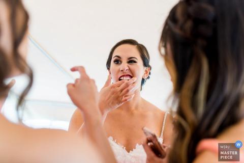 Damigella d'onore che aiuta la sposa a farsi mettere qualcosa nei denti prima del matrimonio a Bear Valley, in California