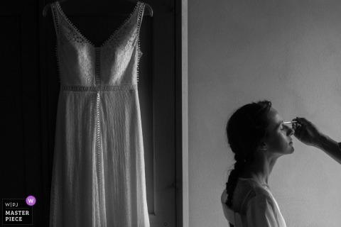 Die Braut schminke sie neben ihrem Hochzeitskleid vor der Hochzeit in Mantova
