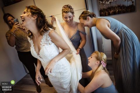 Bruidsmeisjes die de bruid met haar kleding helpen - noordwijkerhout huwelijksfotograaf