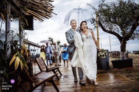 Poza zdjęciem panny młodej i pana młodego, unikając deszczu z parasolem, trzymając suknię panny młodej w Noordwijk
