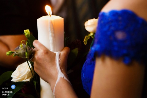 Photo of woman holding a candle as the wax melts onto her hand at the wedding in Slatina, Romania