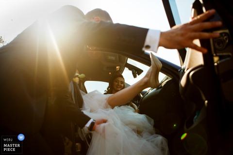Foto al aire libre del novio ayudando a la novia a salir del auto con su vestido de novia en Slatina