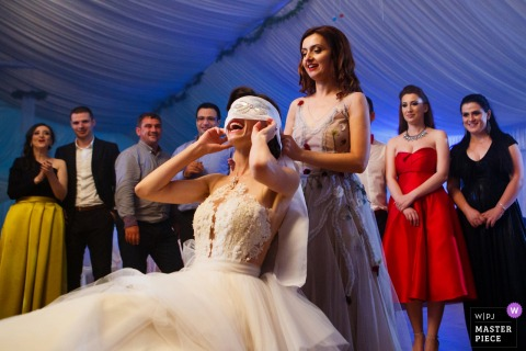 Bridal party having fun with the bride at the wedding reception in Slatina, Romania