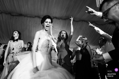 Bride dancing and singing with guests at the wedding reception in Slatina, Romania
