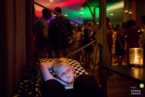 Young boy lays on the couch as guests enjoy the reception