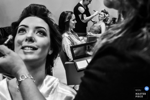 Bride and bridesmaid smile while they get their make up done in Americana