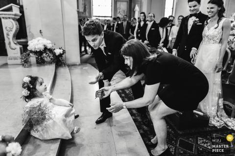 Paris Braut und Bräutigam Lächeln als Gäste versuchen, das Blumenmädchen bei der Hochzeitszeremonie zu bekommen