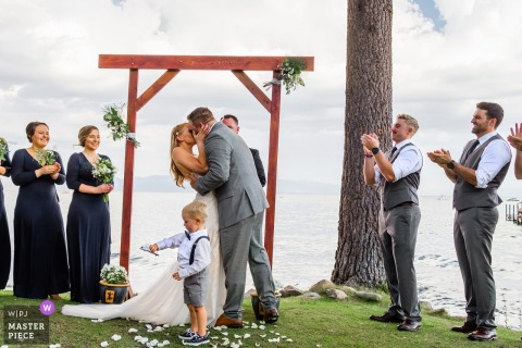 Little boys stands in front of the bride and grooms they kiss outside at the wedding ceremony at Lake Tahoe, CA