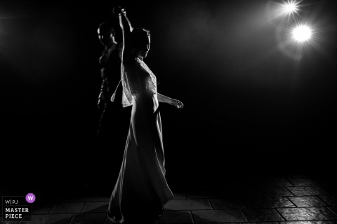 Nantes bride and groom dance at the wedding reception under a single spotlight