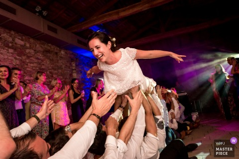 Guests lift up the bride in her wedding dress at the reception in Nantes