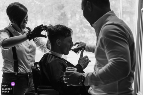 Groom getting a drink while getting a haircut before the wedding ceremony in Russia, Chelyabinsk