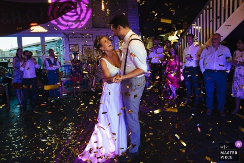 Bride and groom smiles while they dance surrounded by confetti at the wedding reception in east quay, UK
