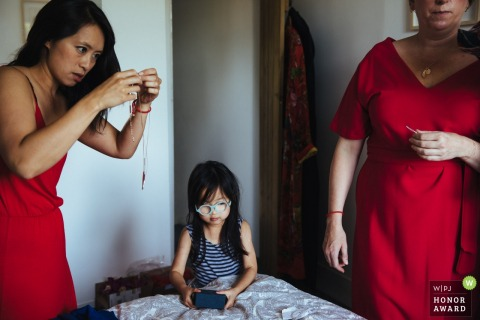Little girl waits while bridesmaids in red dresses finish getting ready at the dreys in the United Kingdom