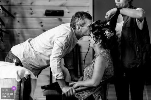 Romania bride gets a kiss on the forehead from her father while she gets her hair ready for the wedding ceremony