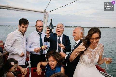 Brautparty, die eine Flasche Champagner draußen auf einem Boot in Venedig, Italien genießt