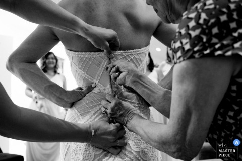Women help the bride with her dress before the wedding ceremony in Sparks Ranch Sonora, CA