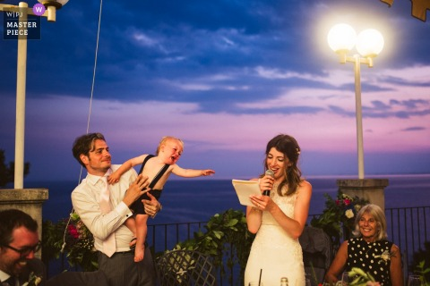 Groom holds child while bride speaks at the wedding reception outside in Triste, Italy